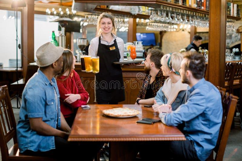 微笑的年轻不同的朋友在户内餐馆和有饮料和啤酒的微笑的女服务员画象  库存照片