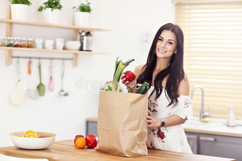微笑的年轻主妇画象在现代厨房里 库存图片