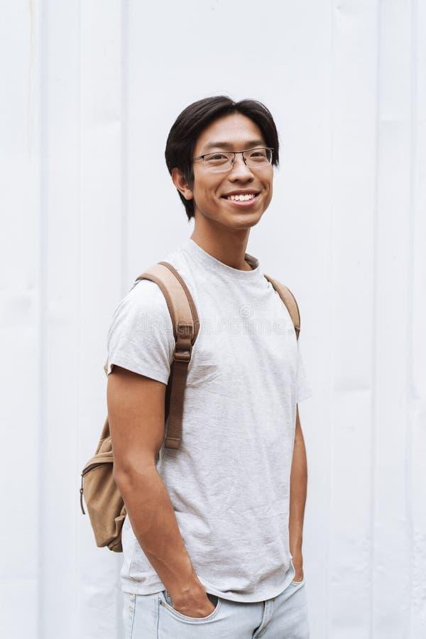 微笑的年轻亚裔人学生运载的背包 免版税库存照片