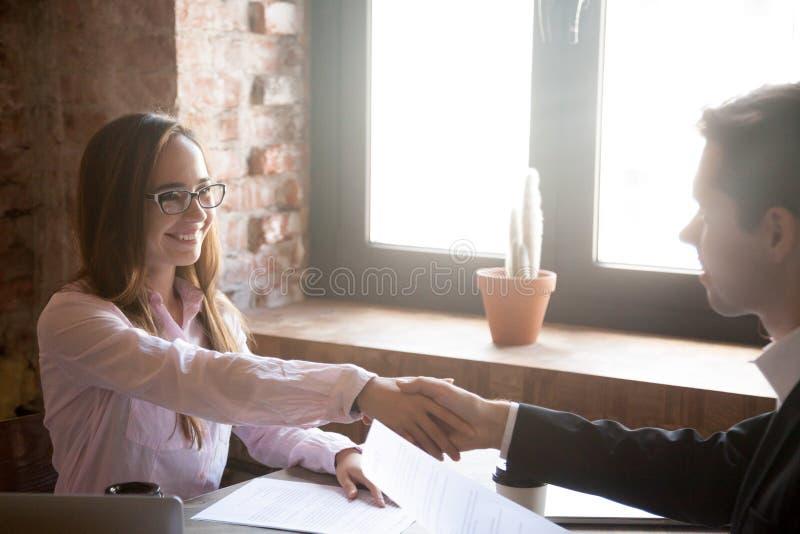 微笑的年轻人和妇女握手,成功的成交 库存图片