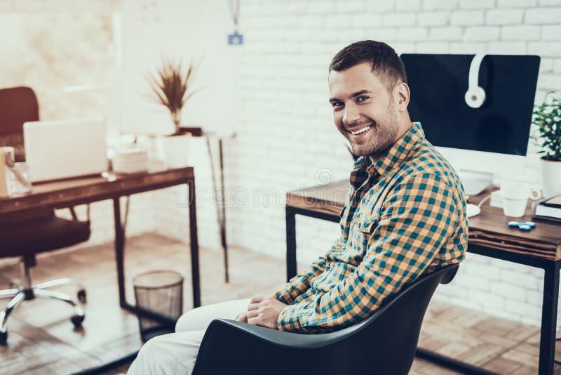 微笑的年轻人坐椅子在办公室 库存图片