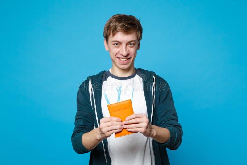 微笑的年轻人画象便服的持护照,在蓝色墙壁背景隔绝的登机牌票 免版税库存图片