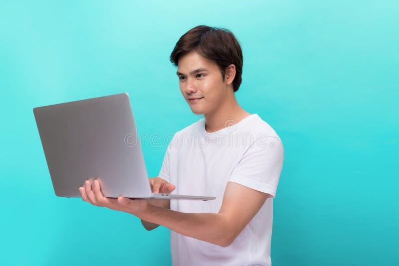 微笑的年轻人画象有在蓝色隔绝的膝上型计算机的 库存图片