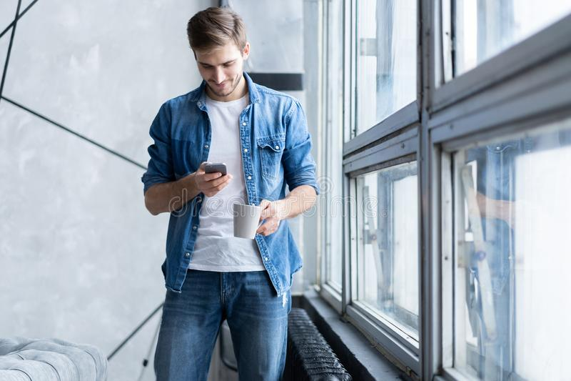 微笑的年轻人谈话在手机,在家看窗口 库存照片