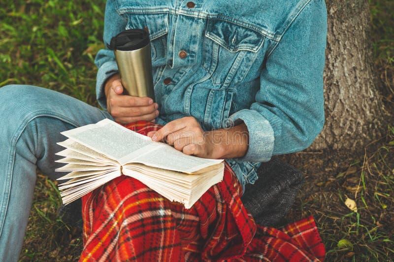 微笑的年轻人阅读书室外与温暖的红色格子花呢披肩和一杯茶背景秋天的假期和生活方式概念 免版税库存图片