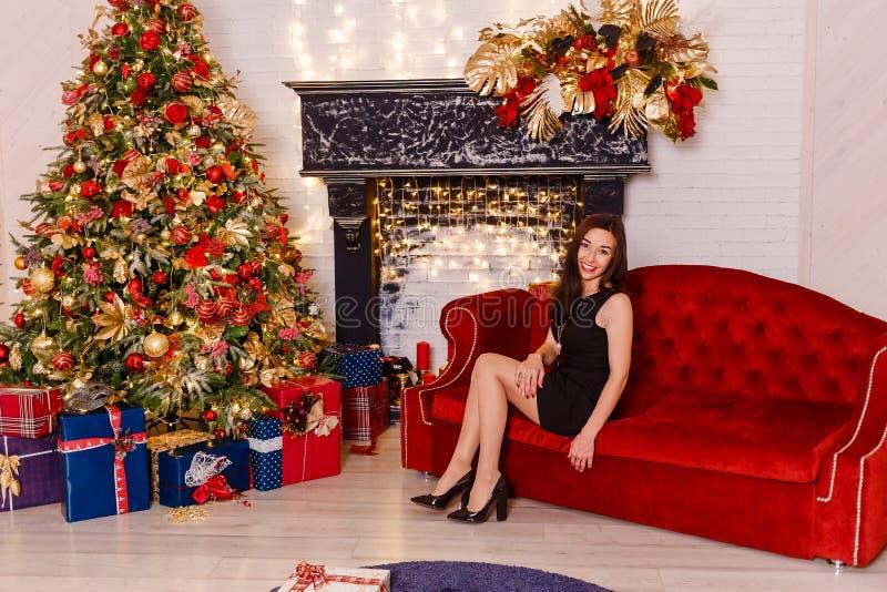 微笑的年轻女人坐在圣诞节的一个红色长沙发 短的黑礼服和黑鞋子的年轻深色的妇女 免版税图库摄影