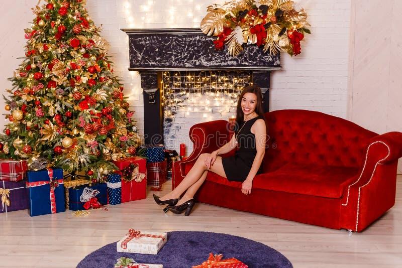 微笑的年轻女人坐在圣诞节的一个红色长沙发 免版税库存照片