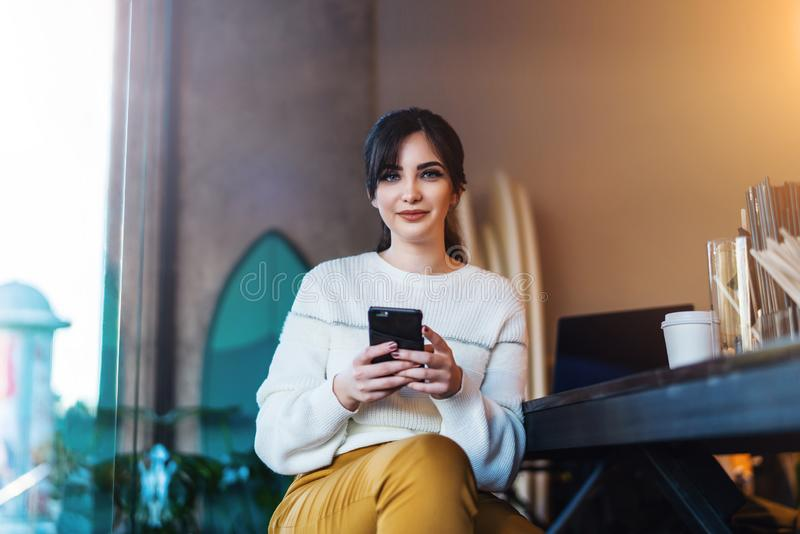 微笑的年轻女人画象有智能手机的在她的手上,坐在咖啡馆的桌上,看照相机 女孩使用智能手机 库存照片