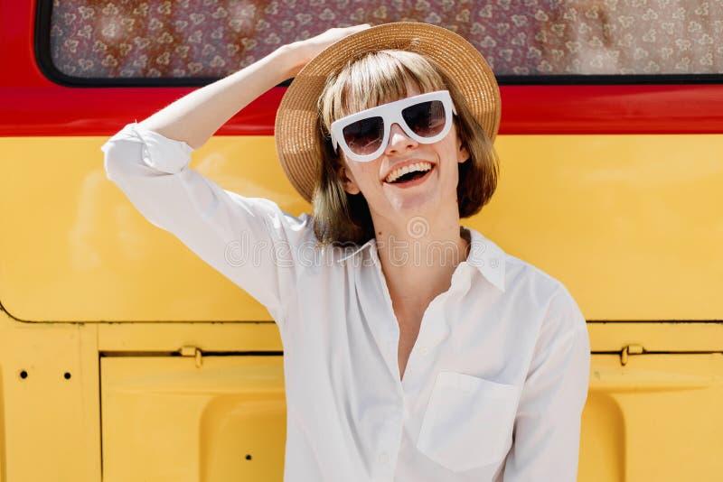 微笑的年轻女人白色太阳镜、一个草帽和白色衬衫姿势的在一明亮红色旁边和黄色 库存照片