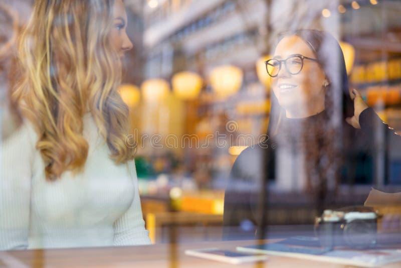 微笑的年轻女人谈话在咖啡馆在通过窗口被看见的城市 库存图片