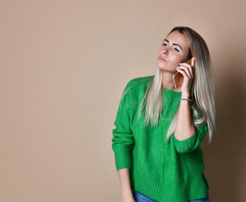 微笑的年轻女人谈话在注视着空白的拷贝空间的手机 免版税库存图片
