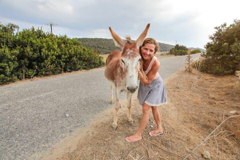 微笑的年轻女人,摆在与野生驴,拥抱他 这些动物在北赛普勒斯土耳其共和国的Karpass地区自由地漫游 免版税库存照片