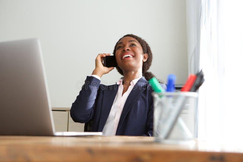 微笑的年轻女商人坐在办公桌和谈话在手机 库存照片