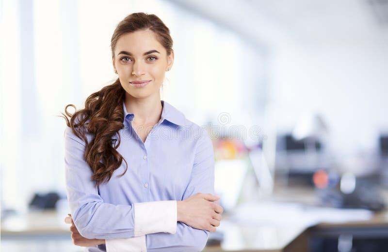 微笑的年轻女实业家画象,当站立在办公室时 库存照片