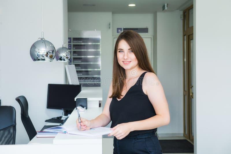 微笑的年轻女性经理身分画象在总台在办公室大厅和文字的在笔记本,记录下来有用 免版税库存照片