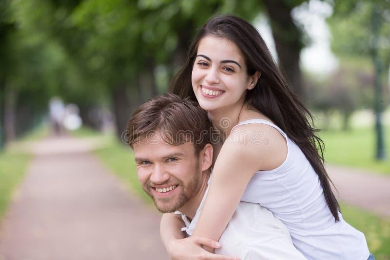 微笑的年轻女朋友肩扛千福年的boyfri画象  免版税库存图片