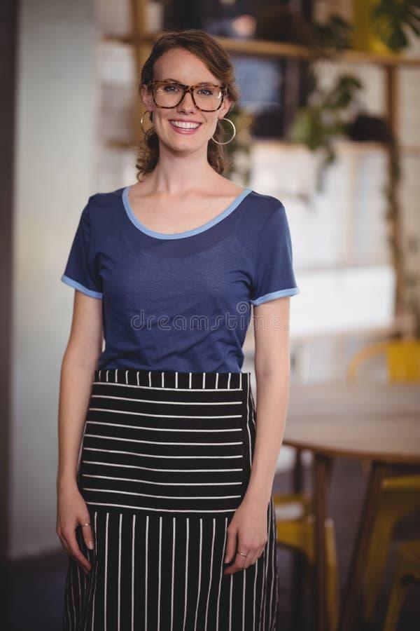 微笑的年轻女服务员佩带的镜片画象在咖啡店 免版税库存图片