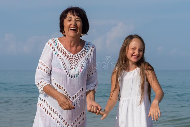 微笑的年轻孙女和年长祖母画象  免版税库存照片