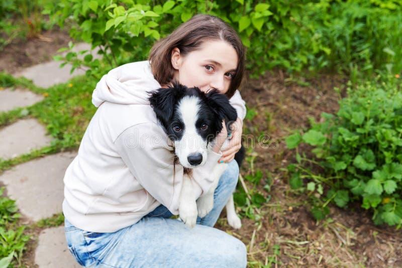 微笑的年轻有吸引力妇女拥抱huging的逗人喜爱的小狗博德牧羊犬在夏天城市公园室外背景中 免版税图库摄影