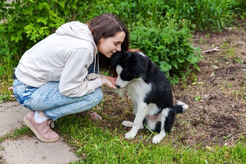 微笑的年轻有吸引力妇女拥抱huging的逗人喜爱的小狗博德牧羊犬在夏天城市公园室外背景中 免版税库存图片