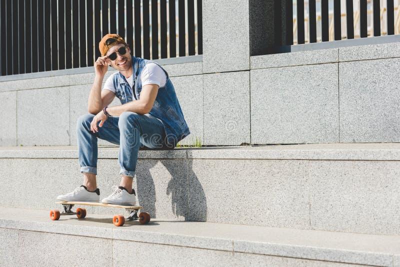 微笑的年轻溜冰者坐有longboard的台阶 图库摄影