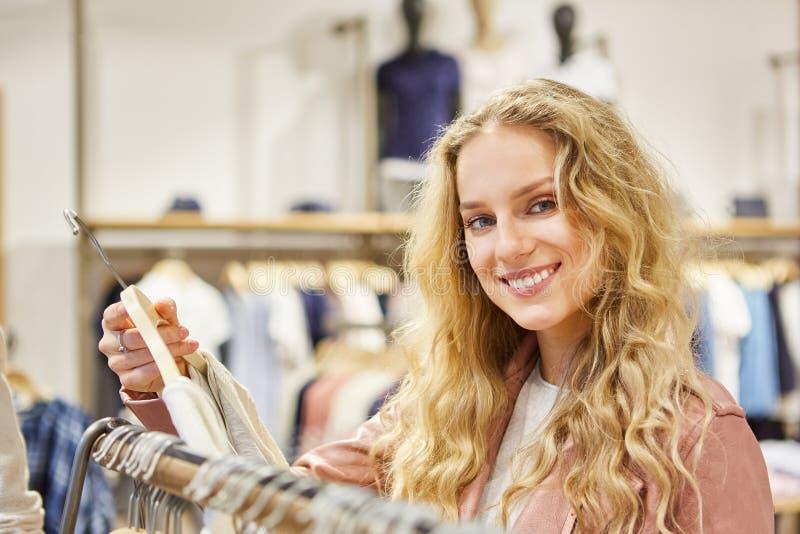 微笑的年轻白肤金发的妇女,当购物时 库存图片