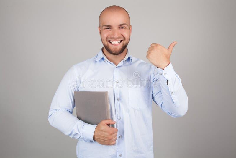 微笑的年轻讨厌的红色有胡子的时髦的学生站立与在纯净的背景和偶然明亮的成套装备的书,指向  库存图片