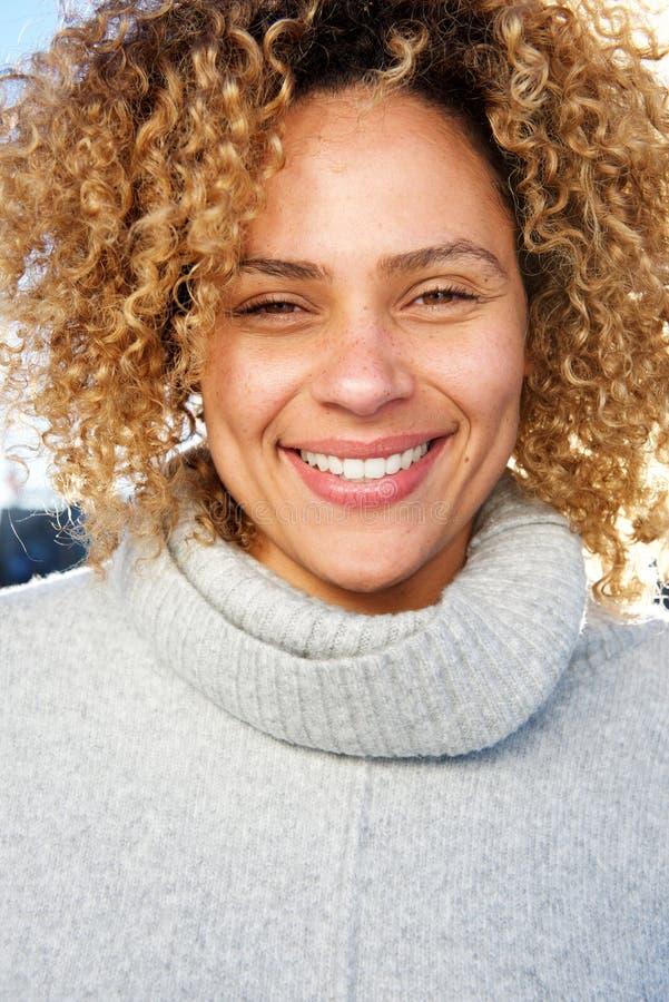 微笑的年轻非裔美国人的妇女的关闭有看照相机的卷发的 库存图片