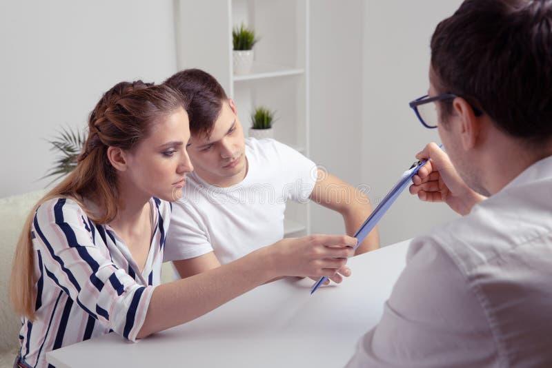 微笑的律师、地产商或财政顾问握手年轻夫妇感谢忠告,保险经纪人或者银行 免版税图库摄影