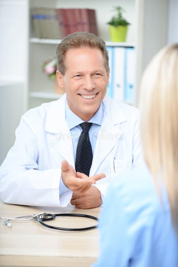 微笑的心脏科医师谈话与患者 库存图片