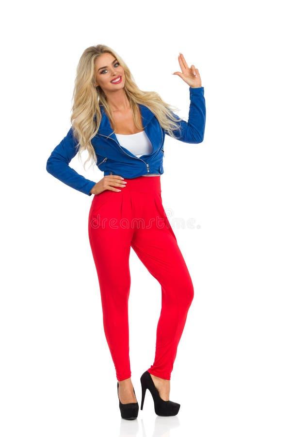 微笑的性感的白肤金发的妇女是站立和显示手枪手标志 免版税图库摄影