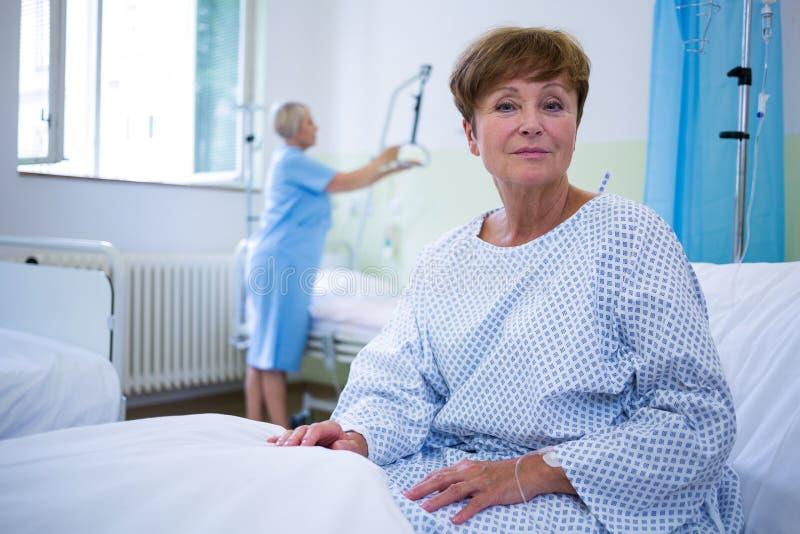 微笑的患者画象坐床 免版税库存图片