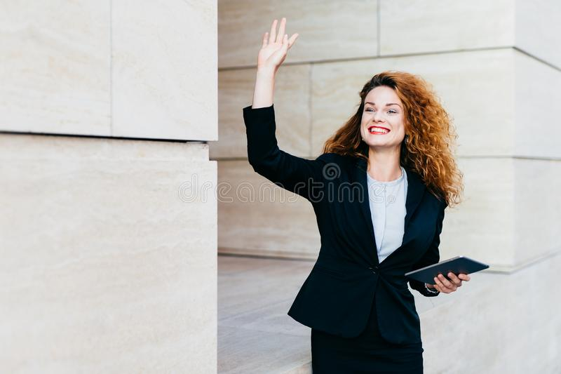 微笑的愉快的女实业家正式地穿戴了,举行在手现代片剂计算机,挥动用她的手,当注意她的com时 库存图片