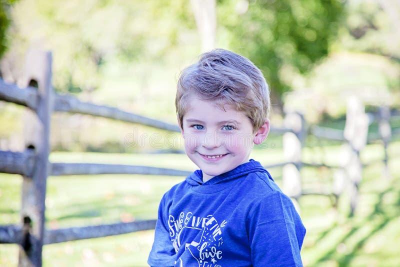 微笑的愉快的男孩的面孔外面 免版税库存照片