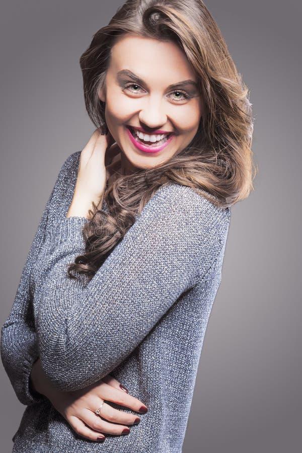 微笑的愉快的笑的深色的妇女画象 反对灰色 免版税库存照片