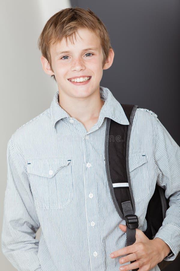 微笑的愉快的活泼的年轻男小学生 库存图片