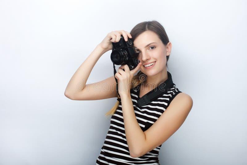 微笑的愉快的年轻美丽的妇女画象摆在与黑照片照相机的镶边衬衣的反对演播室背景 免版税库存照片