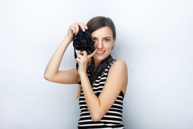 微笑的愉快的年轻美丽的妇女画象摆在与黑照片照相机的镶边衬衣的反对演播室背景 库存图片
