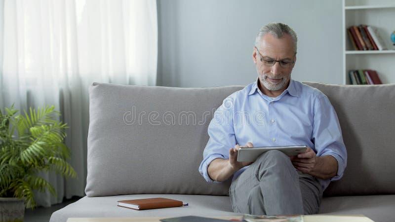 微笑的成人人坐长沙发和观看的家庭照片在片剂 免版税库存图片