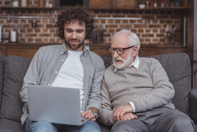 微笑的成人儿子和资深父亲使用膝上型计算机 免版税库存图片