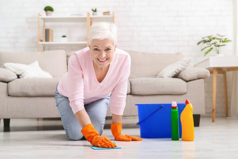 微笑的成熟主妇清洁地板在家 免版税库存图片