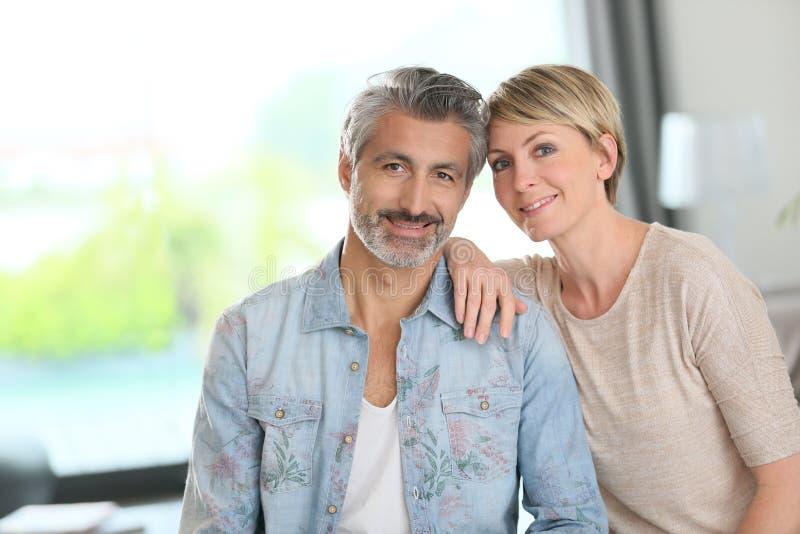 微笑的成熟夫妇在家 图库摄影