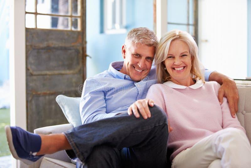 微笑的成熟夫妇画象在家坐沙发 免版税库存照片