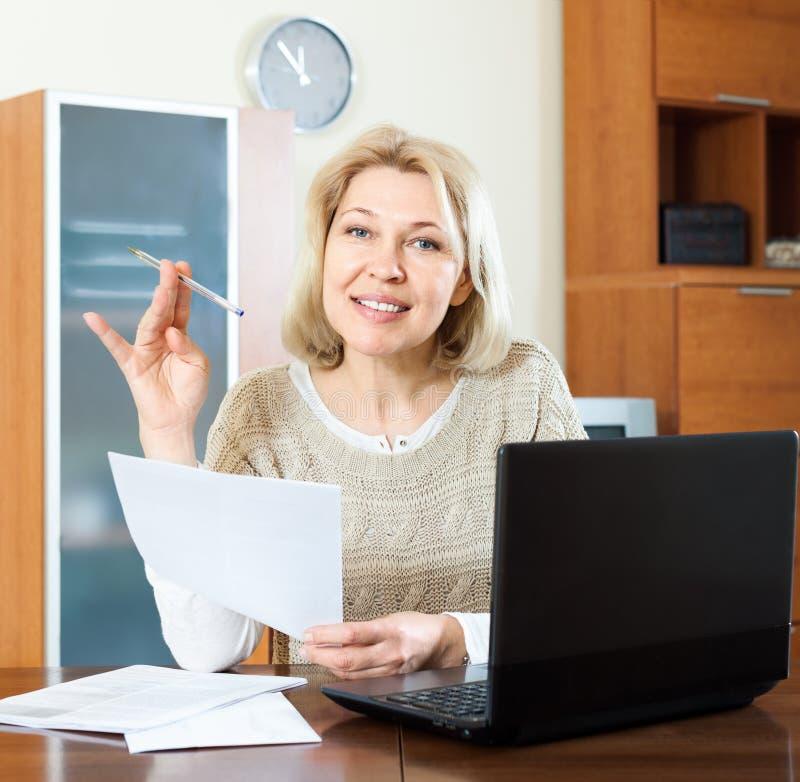 微笑的成熟妇女凝视财政文件 库存照片