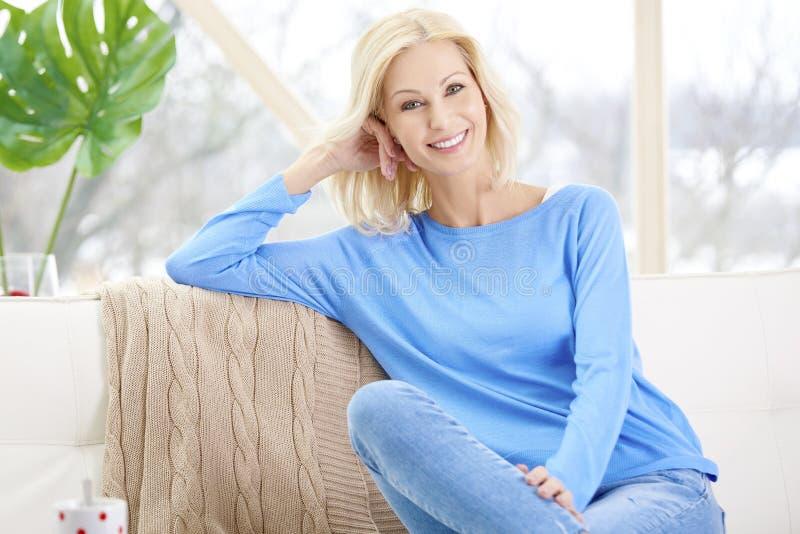 微笑的成熟妇女在家坐沙发 免版税图库摄影