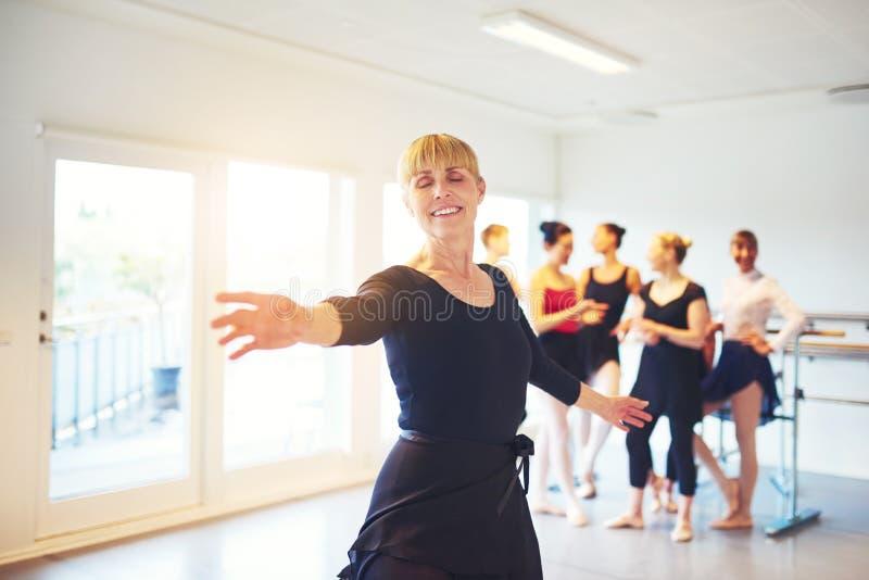 微笑的成熟妇女实践的芭蕾在舞蹈演播室 库存图片