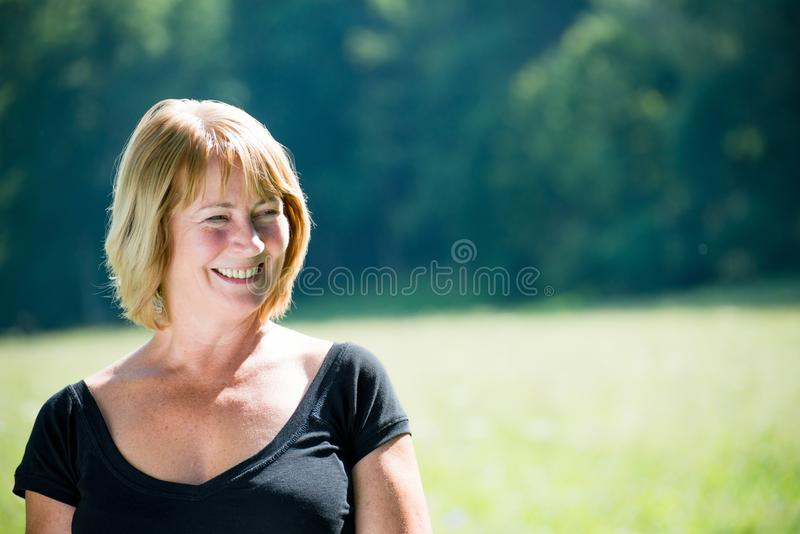 微笑的成熟妇女室外纵向 库存图片