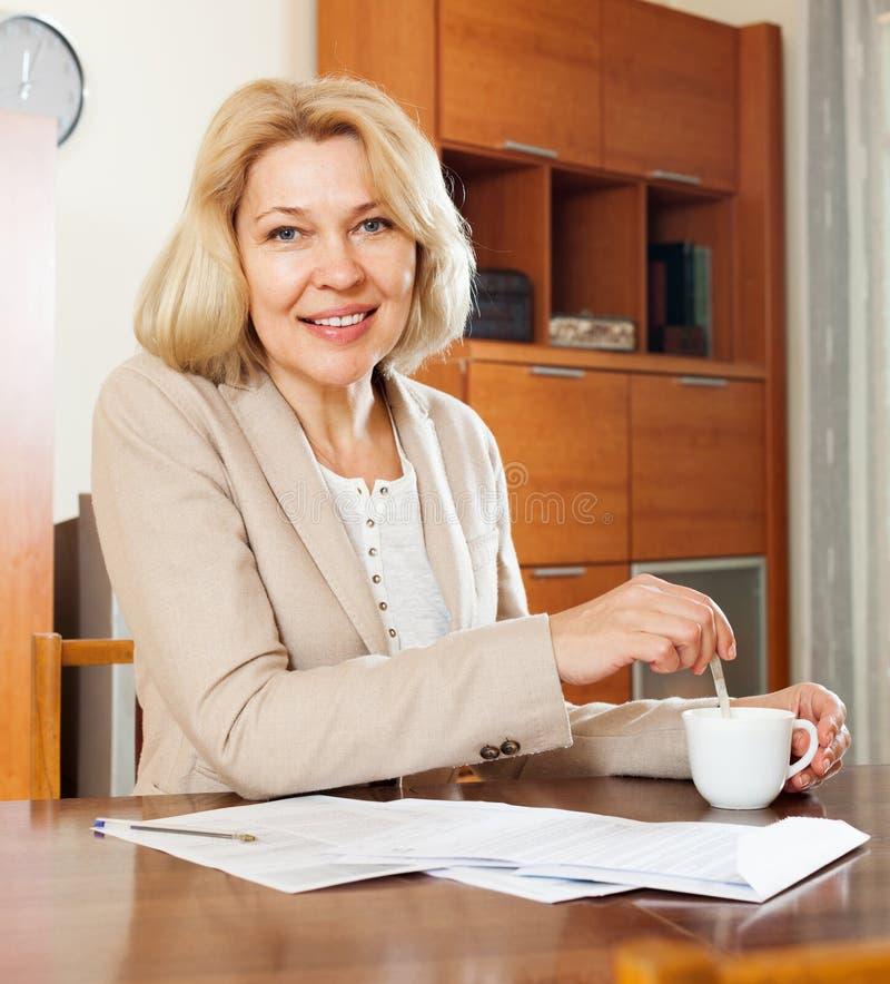 微笑的成熟妇女读书文件在桌上 库存图片