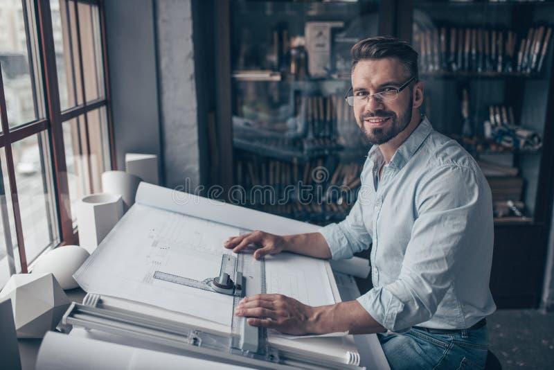 微笑的成熟工程师在工作 库存照片