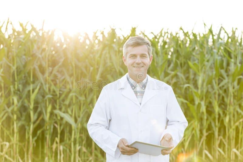 微笑的成熟科学家画象有数字片剂的在玉米农场 免版税库存照片